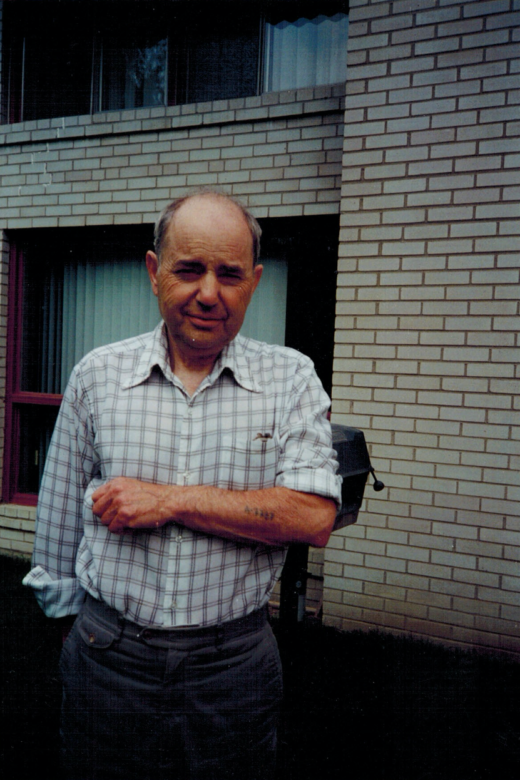 Henry Friedman displaying his tattoo number, A-7727, in front of his house. Toronto, 1984.